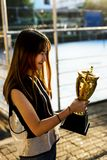 Asian teenage girl in sporty clothes holding a trophy outdoors Royalty Free Stock Photography
