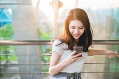 Asian teenage girl is using a smartphone to check flight at the international airport royalty free stock photo