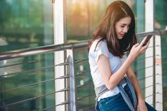 Asian teenage girl is using a smartphone to check flight at the international airport stock photo