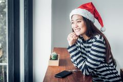 Asian teenage girl wear santa hat and smile face resting her chi Royalty Free Stock Image