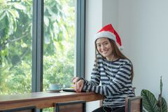Asian teenage girl wear santa hat and smile face resting her chi Stock Image