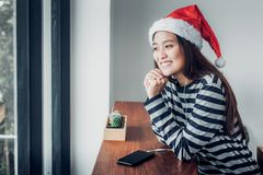 Asian teenage girl wear santa hat and smile face resting her chi Royalty Free Stock Images