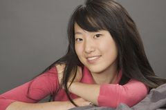 Asian Teenager. Portrait of a beautiful Asian teenager posing on a gray background with some attitude Royalty Free Stock Photos