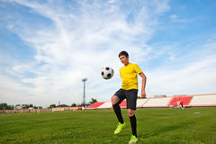 Asian teenager boy in the sports form in a football stadium, practicing. stock photo