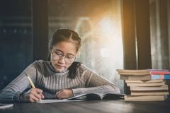 Asian teenager doing school home work in library room royalty free stock photography