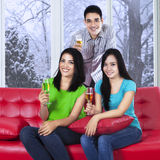 Asian teenager drinking champagne on sofa Stock Image