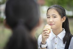 Asian teenager eating icecream cone with happiness face Stock Photo