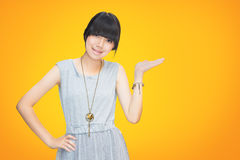 Asian teenager girl showing empty hand. Orange background with clipping path Stock Photo