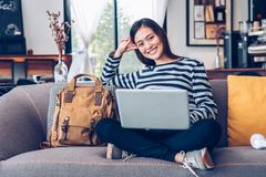 Asian teenager girl using laptop computer and listening music on sofa with happy smiling face at coffee shop,Digital age lifestyle.  royalty free stock image