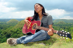 Asian teenager with guitar. Asian long haired teenager playing the guitar and sitting outdoors on grass in front of a tropical hilly landscape Royalty Free Stock Photo