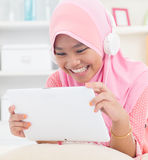Asian teenager listen mp3 headphone. Southeast Asian teenager listen mp3 headphone at home. Muslim teen girl living lifestyle Stock Image