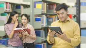 Asian teenager man reads a tablet with girls talk at the book sh. The asian teenager men reads a tablet with girls talk at the book shelf in the background Royalty Free Stock Image