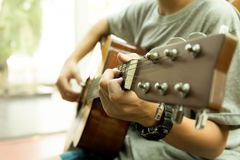 Asian teenager playing the acoustic guitar. Indoors Royalty Free Stock Image
