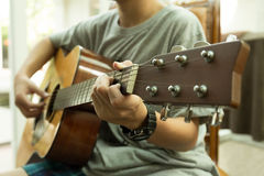Asian teenager playing the acoustic guitar. Indoors Royalty Free Stock Photos