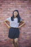 Asian teenager pose like fashion model against red brick wall stock image