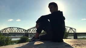 Asian teenager sitting in the street in the background of the bridge. stock video