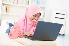 Asian teenager surfing internet. Southeast Asian teenager surfing internet. Muslim teen using notebook at home Royalty Free Stock Photography
