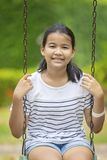 Asian teenager toothy smiling face and sitting on swing in green Royalty Free Stock Image