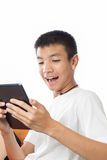 Asian teenager using his tablet with happy feeling Royalty Free Stock Photos