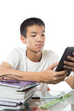 Asian teenager using his tablet over the pile of books Royalty Free Stock Photos