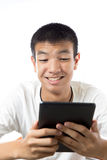 Asian teenager using his tablet with smile Royalty Free Stock Image