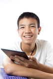 Asian teenager using his tablet with smile Stock Photos