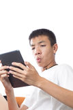 Asian teenager using his tablet with the surprise Royalty Free Stock Image