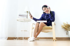 Asian teenager wearing headphone and holding mobilephone. A beautiful Asian teenage female wearing headphone and holding smartphone with feeling cheerful and Royalty Free Stock Photo
