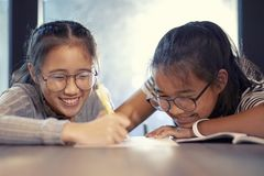 Asian teenager writing by pen on white paper and toothy smiling with happiness emotion stock photo