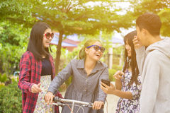 Asian teenagers. Group of asian teenager walking in the park and enjoyed watching video from smartphone Stock Photos