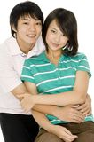 Asian Teens. A young asian couple sitting together on white background royalty free stock photos