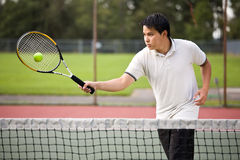 Asian tennis player. An asian tennis player hitting the ball Royalty Free Stock Photo