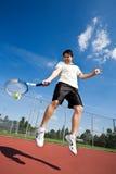 Asian tennis player. An asian tennis player jumping in the air hitting tennis ball Stock Photography