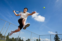 Asian tennis player. An asian tennis player jumping in the air hitting a tennis ball Royalty Free Stock Photography
