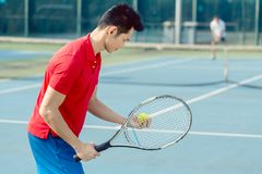 Asian tennis player looking at the ball with concentration before serving. Side view of a determined Asian tennis player looking at the ball with concentration Stock Images