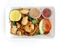 Asian thai ethnic food takeaway. An image of a Thai dish packed in takeout containers.  Dish is Fried flat Rice Noodles with seafoods, a very popular dish in Royalty Free Stock Image