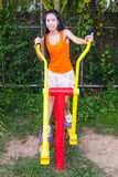Asian Thai Girl with Exercise Machine in Public Park Stock Photo
