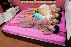 Asian Thai girls and boy sleep on ones side with e Royalty Free Stock Photos