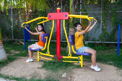 Asian Thai Girls with Exercise Machine in Public Park Stock Photography