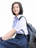 Asian Thai high schoolgirl student in school uniform isolated. Cute Asian Thai high schoolgirl student in school uniform sitting with her backpack showing stock photos