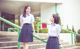 Asian Thai high schoolgirls student couple in school. Cute Asian Thai high schoolgirls student couple in school uniform sit on the stairway chatting with a happy stock images