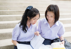 Asian Thai high schoolgirls student couple in school reading and study Royalty Free Stock Image