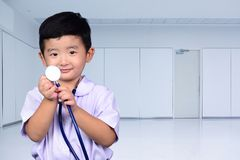 Asian Thai kid with medical stethoscope looking at camera, healt. Hy concept idea stock photo