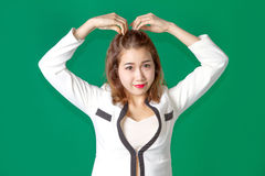 Asian Thai lady officer with business wear acting. Asian thai lady acting arm on head like heart symbol in businees wearing on green screen Stock Images