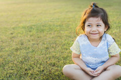 Asian Thai little Cute Girl Making Meditation and Practicing Yog. Asian Thai little Cute Girl Smiling and Practicing Yoga in Garden with Morning Light Beam Royalty Free Stock Photos