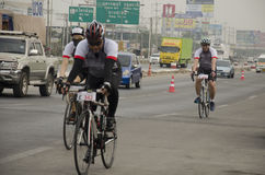 Asian thai people biking bicycle in race on street highway with traffic road Stock Image