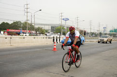 Asian thai people biking bicycle in race on street highway with traffic road Royalty Free Stock Images