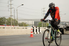 Asian thai people biking bicycle in race on street highway with traffic road Stock Photos