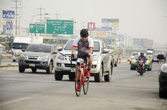 Asian thai people biking bicycle in race on street highway with traffic road Royalty Free Stock Photography