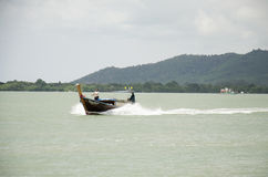 Asian thai people driving wooden motor boat on the sea for send Stock Photo